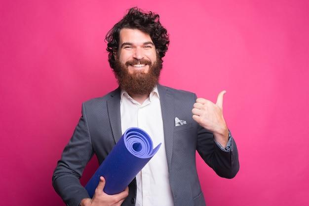 Молодой счастливый человек показывает палец вверх и держит коврик для йоги