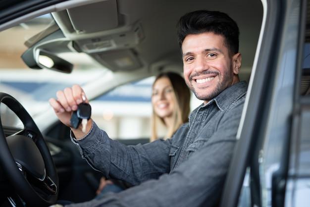 カーディーラーのサロンで彼の新しい車のキーを示す若い幸せな男