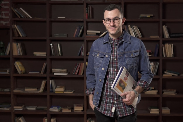 Young happy man student holding a book in front of the bookcase