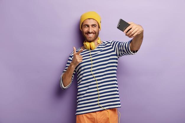 若い幸せな男は自分撮りを取り、ビデオ通話を行い、スマートフォンのカメラを指さします