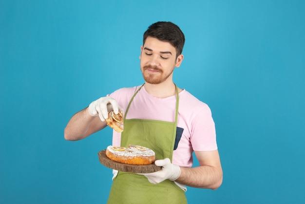 Fetta di torta di takin del giovane uomo felice su un blu.