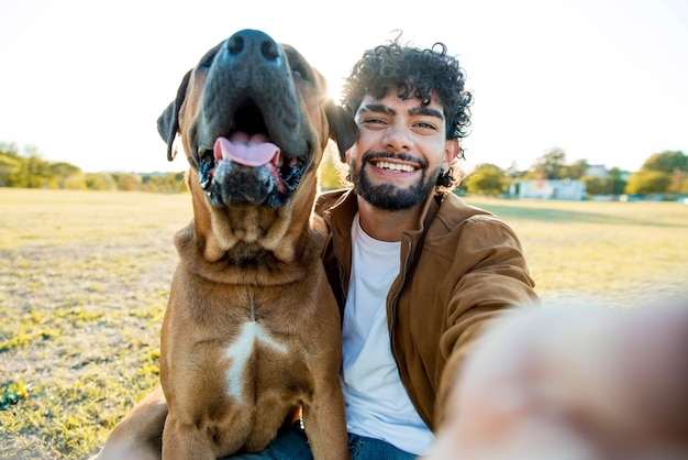 公園で犬と一緒に自分撮りをしている若い幸せな男-屋外で一緒に楽しんでいる笑顔の男と子犬-人間と動物の概念間の友情と愛