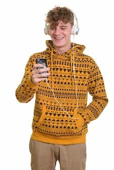 Молодой счастливый человек с помощью мобильного телефона и наушников