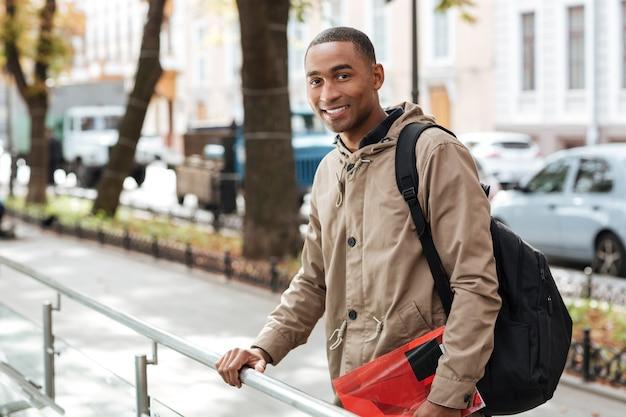 책을 들고 정면을 보면서 거리에 서있는 배낭을 입고 젊은 행복한 사람