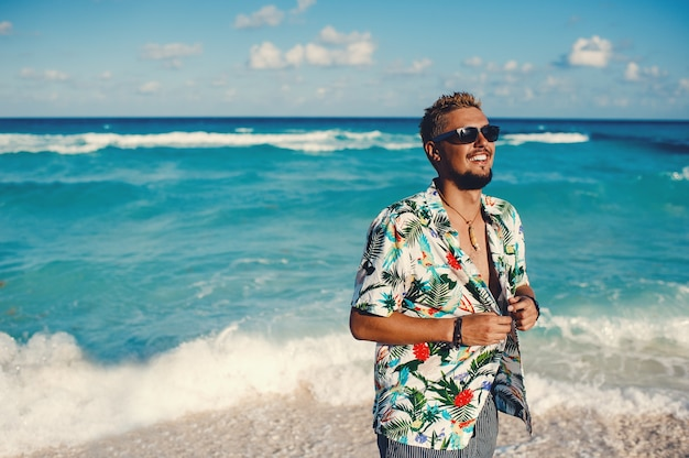 Молодой счастливый человек в гавайской рубашке на фоне моря или океана