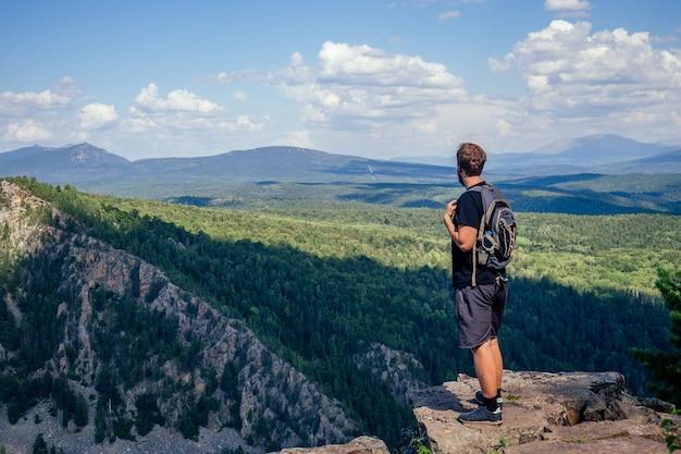 岩の上に立っているバックパックを持つ若い幸せな男