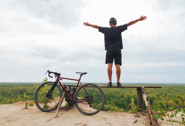 Young happy man with a bicycle stands on a cliff and enjoys the view with outstretched arms.
