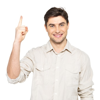 Young happy man with good idea sign  in casuals isolated on white wall.