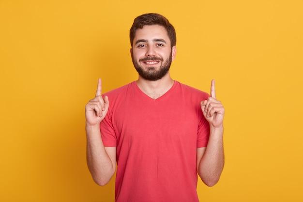 良い気分で若い幸せな男、黄色に分離されたポーズ、彼の人差し指で上向き、笑顔を探しています。広告や宣伝のためのスペースをコピーします。