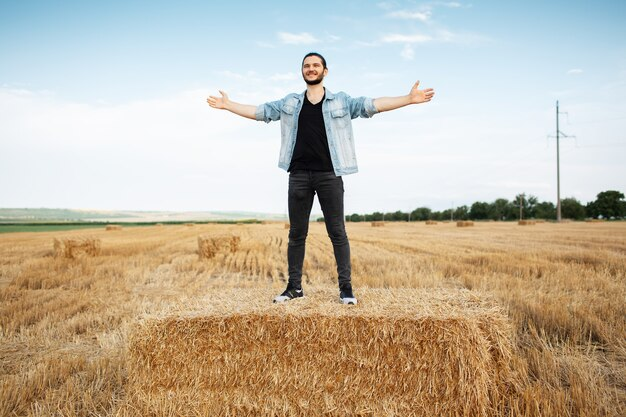 Young happy man with hands up standing on haystacks in wheat field.