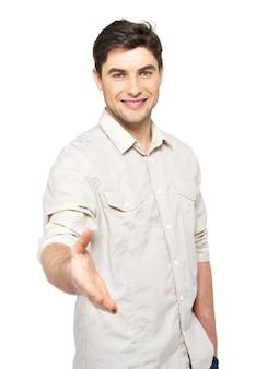 白い壁に隔離されたカジュアルな握手ジェスチャーで若い幸せな男。