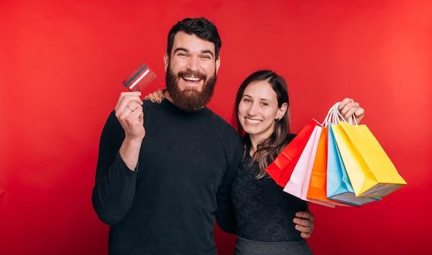 Молодой счастливый человек со своей подругой смотрят на камеру. молодая женщина держит несколько сумок, а парень держит кредитную карту.