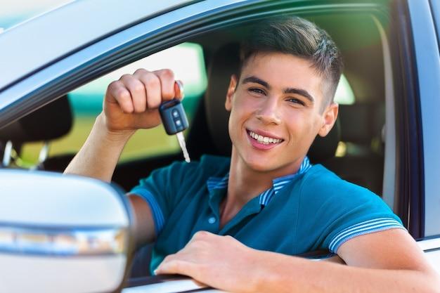웃는 차에 열쇠를 가진 젊은 행복한 남자 자동차 구매의 개념