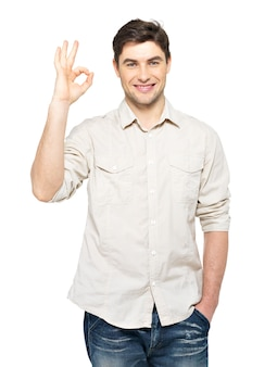 白い壁に隔離されたカジュアルなサインインokの若い幸せな男。