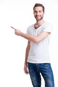 と若い幸せな男は、カジュアルで横に指を示しています-白で隔離。