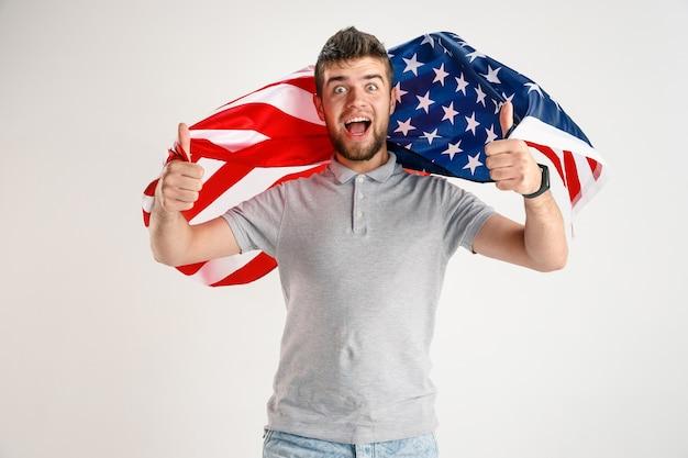 白いスタジオで隔離のアメリカ合衆国の旗を持つ若い幸せな男。