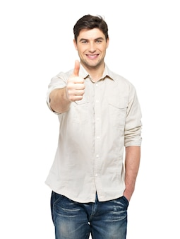 Il giovane uomo felice con i pollici aumenta il segno in casuals isolato sulla parete bianca.