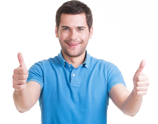 Young happy man with thumbs up sign in casuals isolated on white wall.