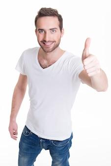 Il giovane uomo felice con i pollici aumenta il segno nei casuals isolati
