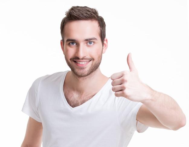 Молодой счастливый человек с большими пальцами руки вверх подписывается в повседневной одежде, изолированной на белом фоне.