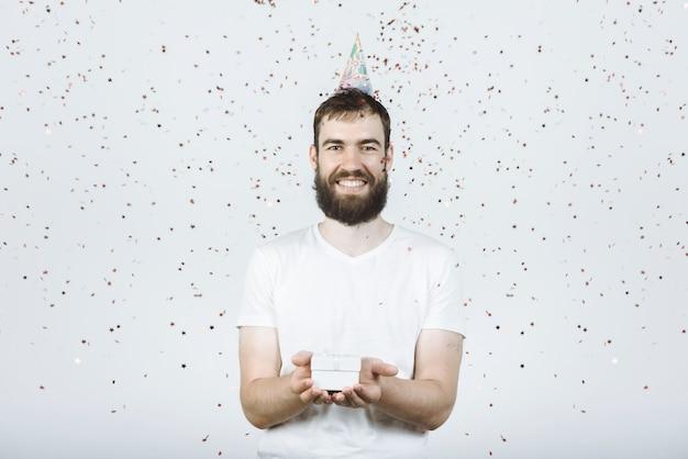 흰색 티셔츠에 파티 모자에 웨이드와 젊은 행복한 사람은 색종이와 회색에 선물을 들고있다