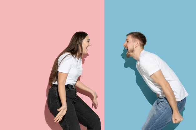 Young and happy man and woman in casual clothes on pink, blue bicolored wall, dancing