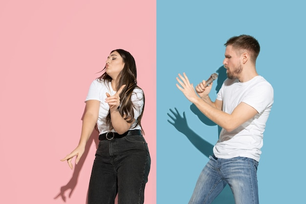 Young and happy man and woman in casual clothes on pink, blue bicolored wall, singing and dancing