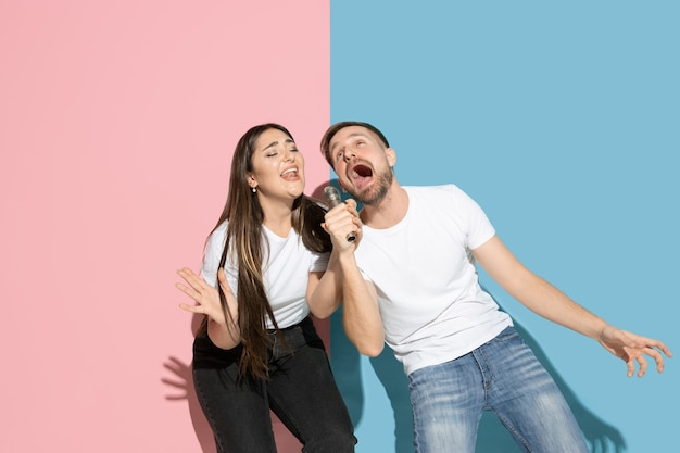 Young and happy man and woman in casual clothes on pink, blue bicolored wall, singing