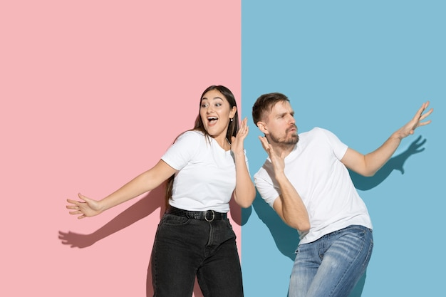 Young and happy man and woman in casual clothes on pink and blue bicolored wall