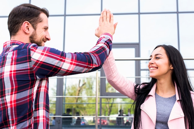 Young happy man and woman friends giving high five near glass building