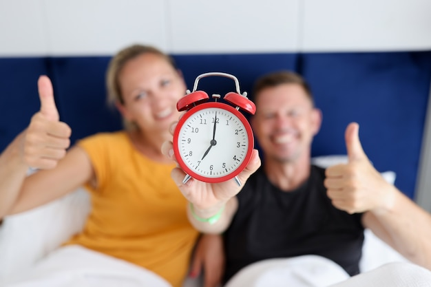 Young and happy man and woman holding red alarm clock and thumbs up while lying in bedroom