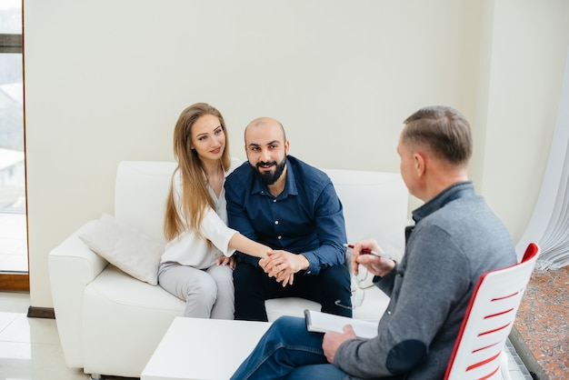 A young happy married couple of men and women talk to a psychologist at a therapy session. psychology.