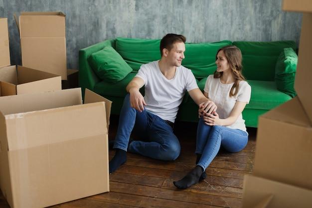 若い幸せなミレニアル世代のカップルの学生は彼らの最初の新しい所有者の家に移動します