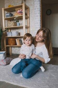 Молодая счастливая мама играет со своей маленькой дочкой дома на полу. семейное счастье