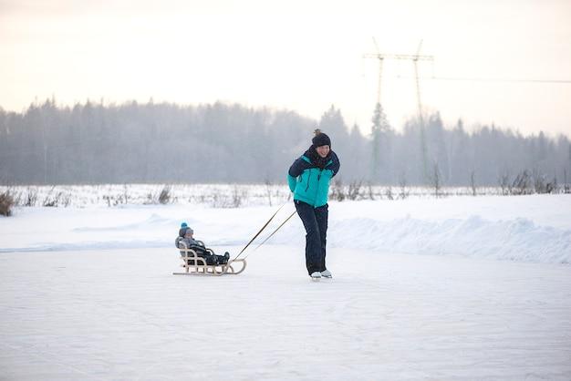 若い幸せな母と小さな男の子の息子が一緒に雪の冬の湖でそり