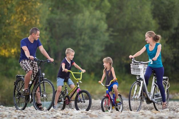 若い幸せな母、父、2人のかわいい金髪の子供、男の子と女の子のぼやけた明るい夏の日の背景に小石の川の土手で自転車に乗って。アクティブなライフスタイルと家族のレクリエーションの概念。