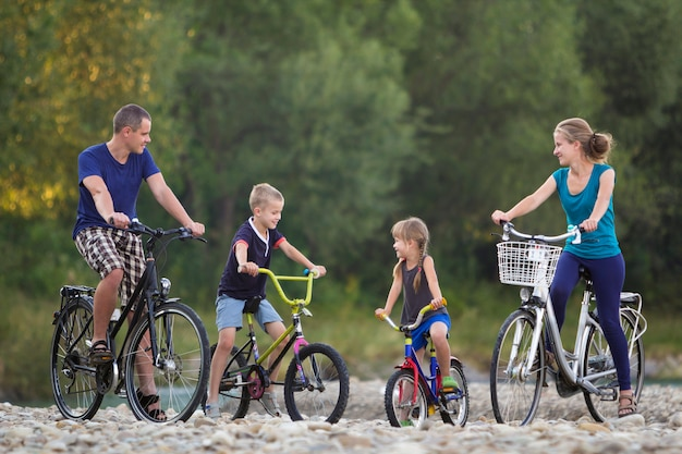Young happy mother, father and two cute blond children, boy and girl riding bicycles on pebbled river bank on blurred bright summer day background. active lifestyle and family recreation concept.