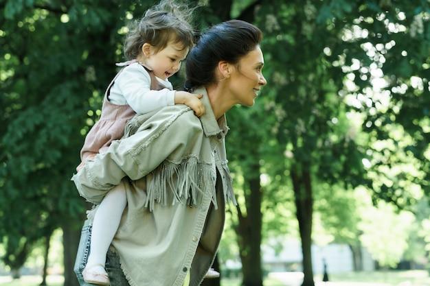 Молодая счастливая мать подвезла свою маленькую дочь на спине