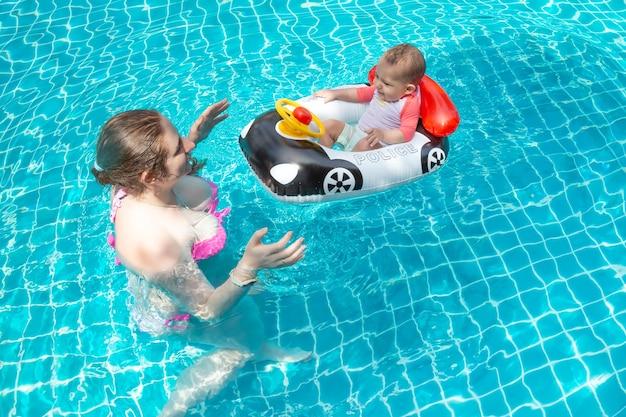 若い幸せな母親はプールで赤ちゃんと一緒に楽しんでいますうれしそうな小さな子供は膨脹可能なボートの車に座っています