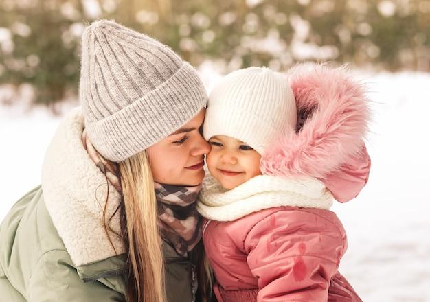 冬の若い幸せな母親は、彼女の小さな娘を腕に抱き、彼女を見ています。家族写真。母性と子供時代