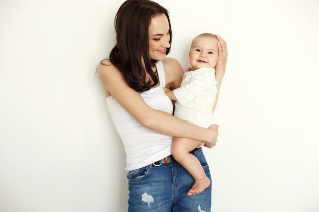 Holding sorridente della giovane madre felice che esamina sua figlia del bambino sopra la parete bianca.