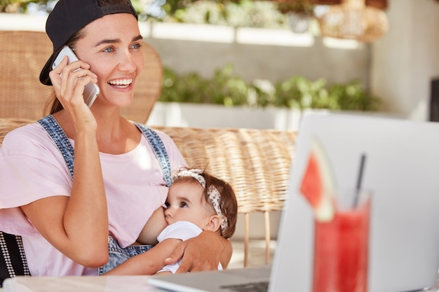 Young happy mother in stylish cap and casual clothing, breastfeeds her little child, gives breastmilk, talks with someone via smart phone and watches video for unexperienced parents on laptop computer