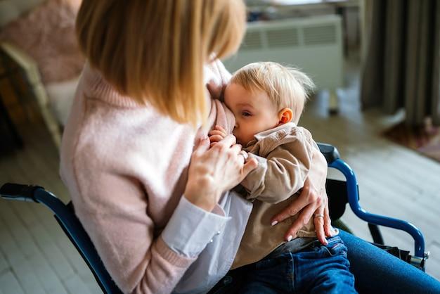 Молодая счастливая мать с инвалидностью в инвалидной коляске кормит ребенка грудью дома