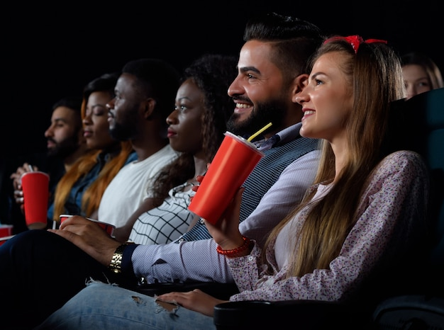 Young happy multicultural friends relaxing at the movie theatre