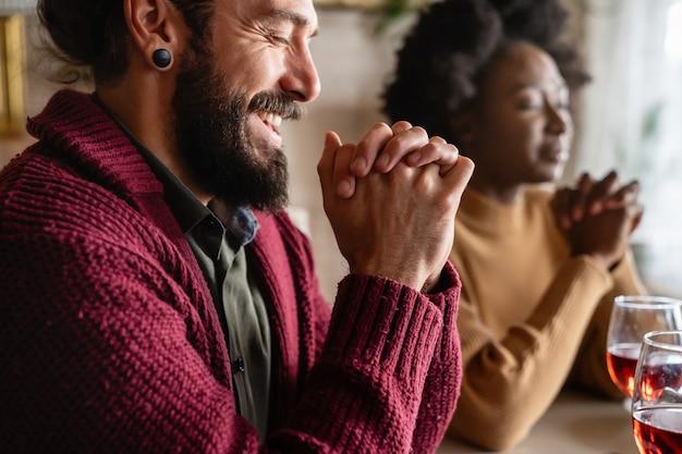 주님께 그들의 음식과 하루를 축복해 달라고 간구하는 젊은 행복한 다민족 부부