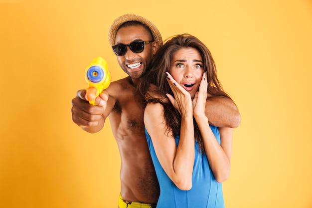 오렌지 벽에 절연 물 총을 가지고 노는 재미 젊은 행복 다민족 부부