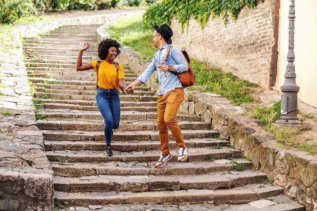 階段を走り、街の古い部分で楽しんでいる若い幸せな多民族のカップル