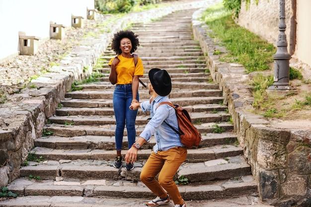 Молодая счастливая многорасовая пара бегает по лестнице и веселится в старой части города