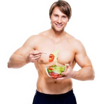 Молодой счастливый мускулистый мужчина ест салат над белой стеной.
