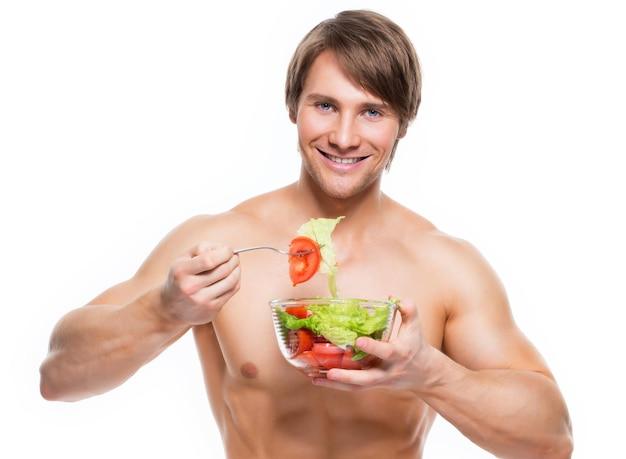 Giovane uomo muscolare felice che mangia un'insalata sopra il muro bianco.